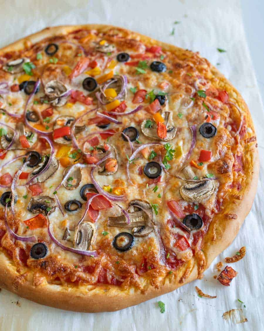 whole homemade veggie pizza with olives red onion mushrooms on parchment
