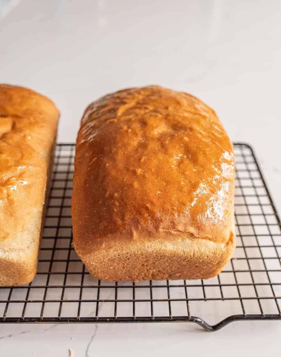 buttered loaf of bread on cooling rack