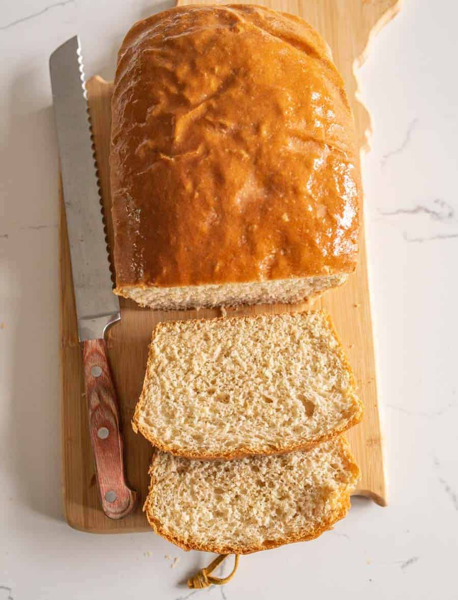 loaf of bread with knife on cutting board