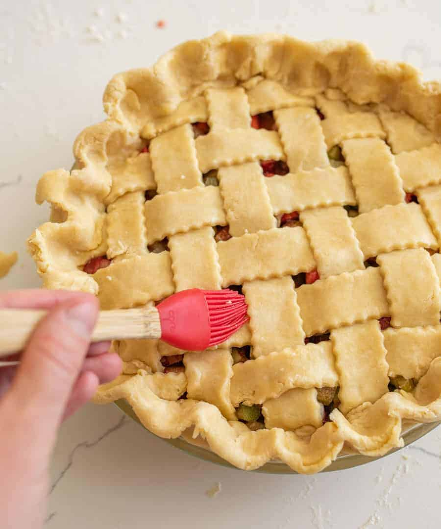 red pastry brush adding water to top of latticed pie crust