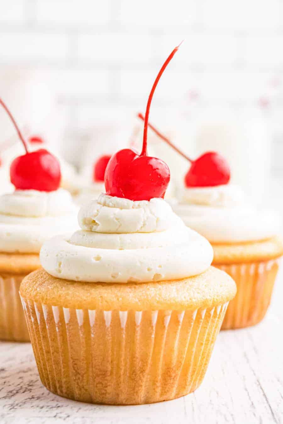 cluster of close up cherry chip cupcakes with maraschino cherries on top of each on