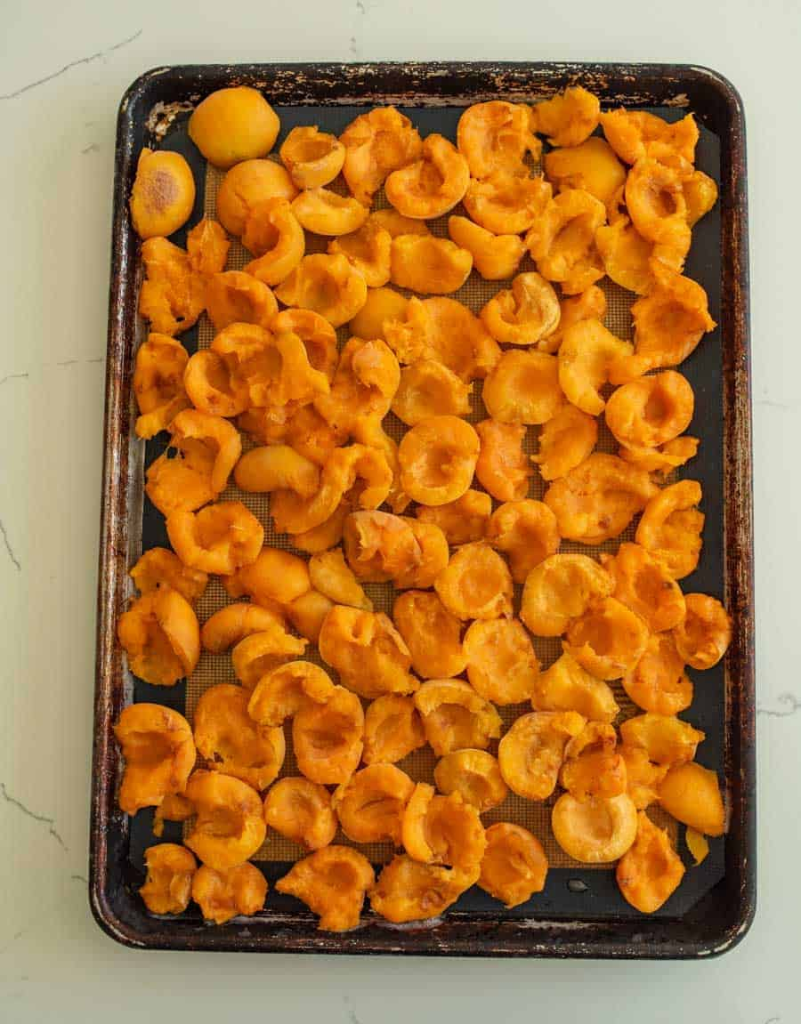 halved apricots on baking sheet