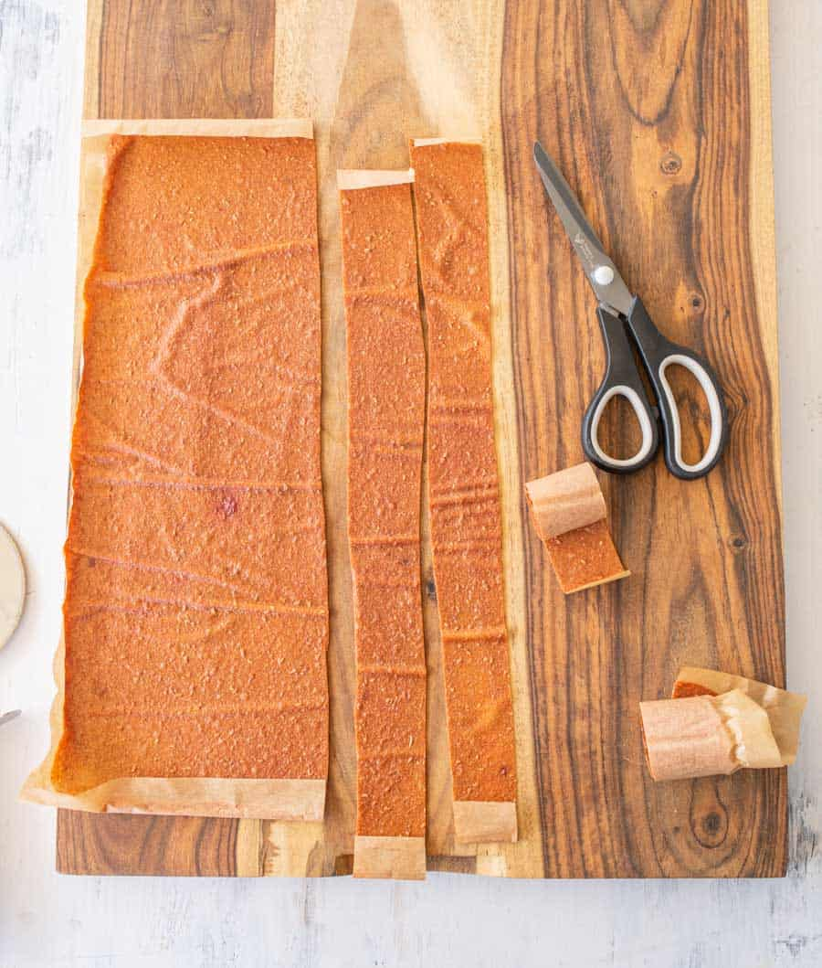 cutting finished fruit leather into strips with scissors