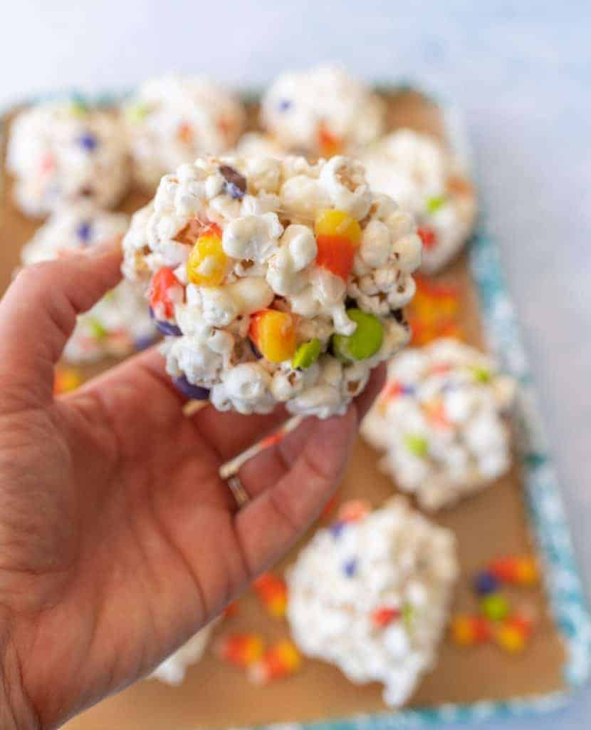 halloween popcorn balls with candy corn in hand