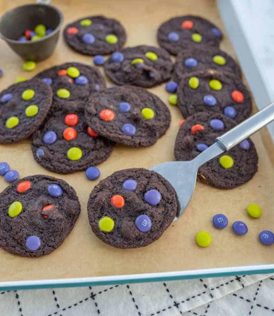 baking sheet filled with dark chocolate halloween M&M cookies