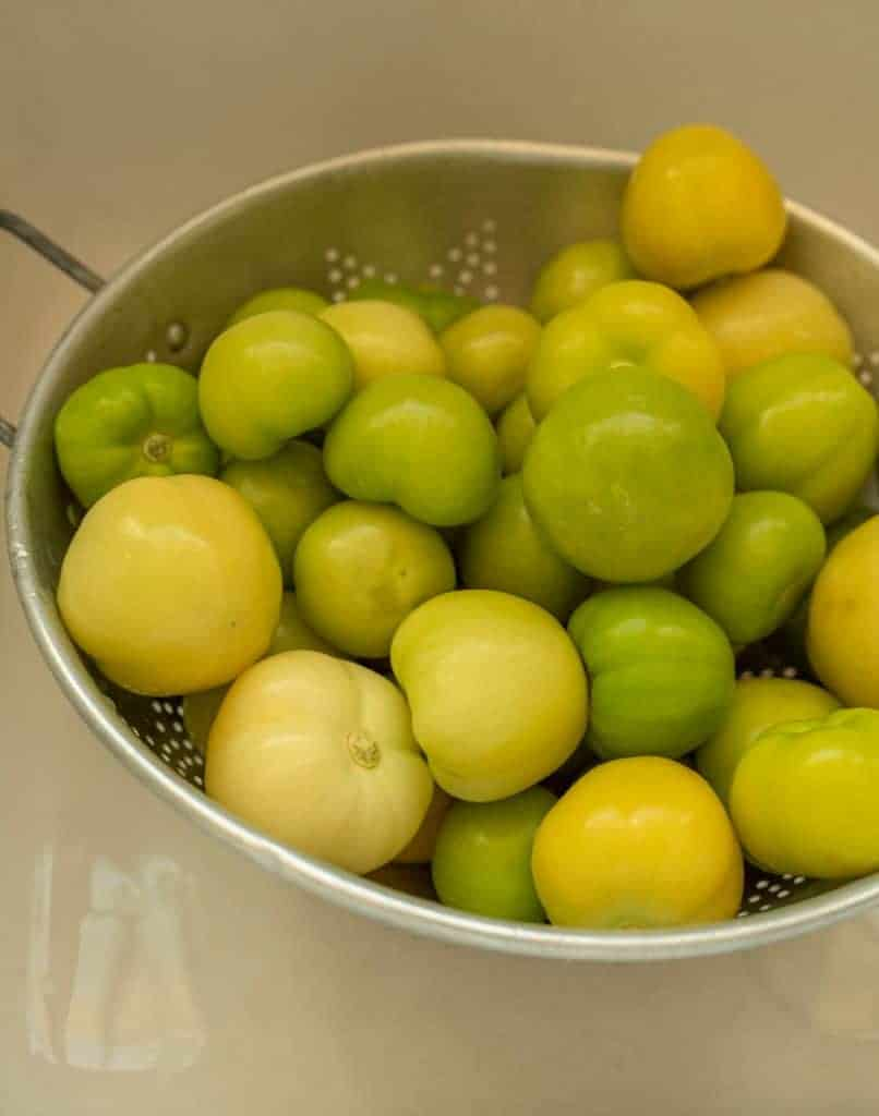 colander of peeled tomatillos being washed in a white sink