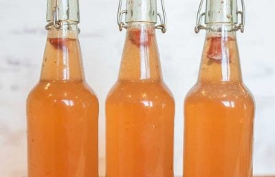 thee wire lid carafe bottles of orange second ferment kombucha with oranges and cherries in the bottom