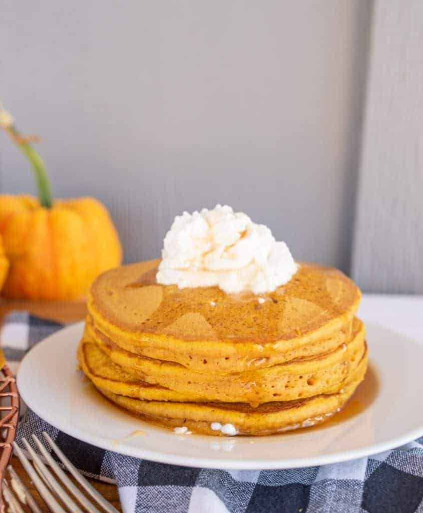 pile pf pumpkin pancakes on white plate with whipped cream