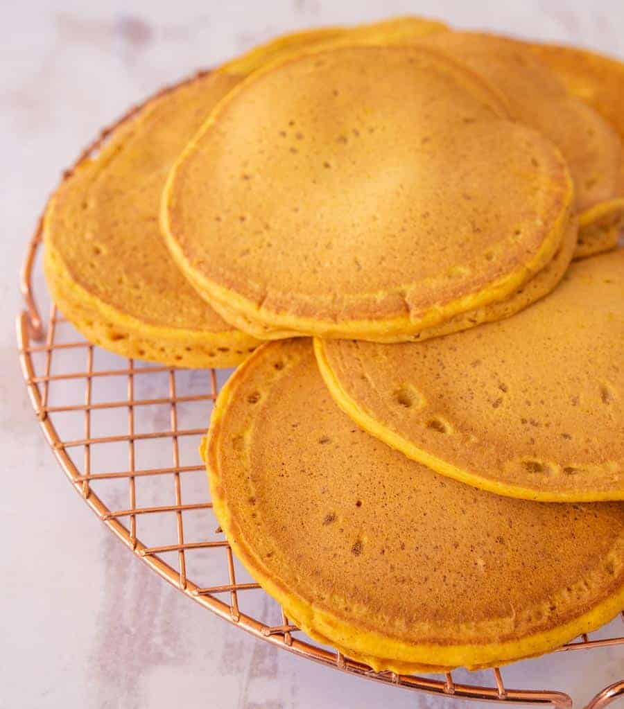 6 golden orange pancakes on a cooling rack