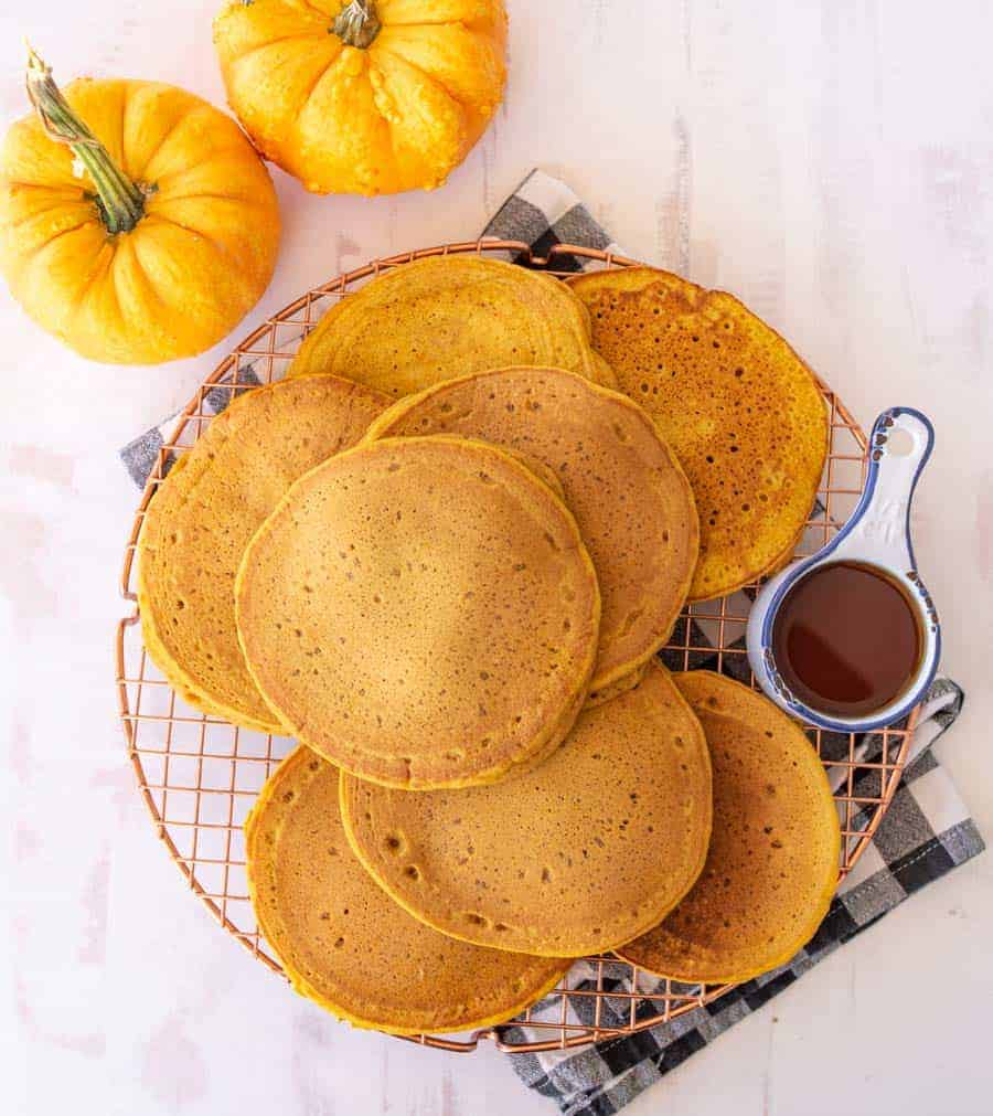 pumpkin pancakes resting on a copper round cooling rack