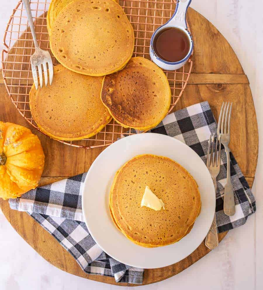 pancakes on cooling rack and some on a plate with butter