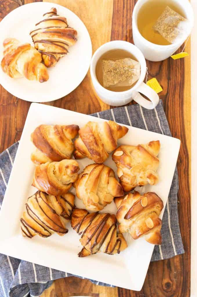 three kinds of croissants on a white plate with tea