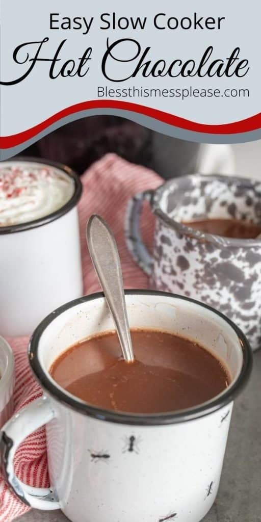 "Picture of a white mug of hot chocolate with a spoon in it and a few mugs in the background and the words ""easy slow cooker hot chocolate"" written at the top"