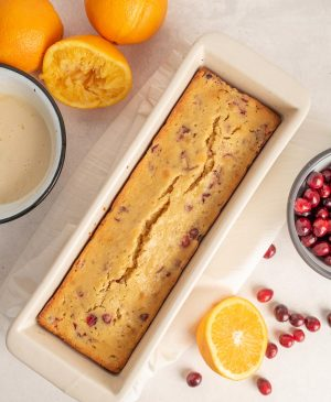 loaf of cranberry orange bread in white loaf pan surrounded by oranges and cranberries