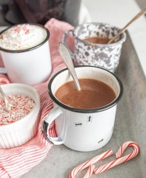 mugs filled with crock pot hot chocolate with a spoon in them
