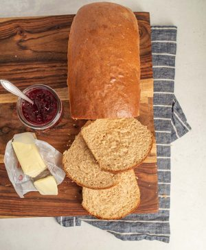 top view of whole wheat bread loaf with three slices cut with butter and jam next to it