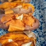 four baked sweet potatoes with butter on them in a baking dish