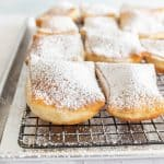 close up of beignets dusted with powdered sugar on a tray
