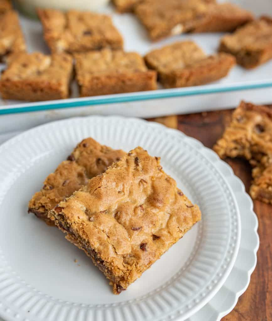 close up of a plate of blondies with a pan of blondies in the background