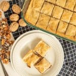 top view of a plate and pan of baklava with walnuts around them