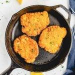 crispy fried pork chops in a cast iron skillet with lemon slices