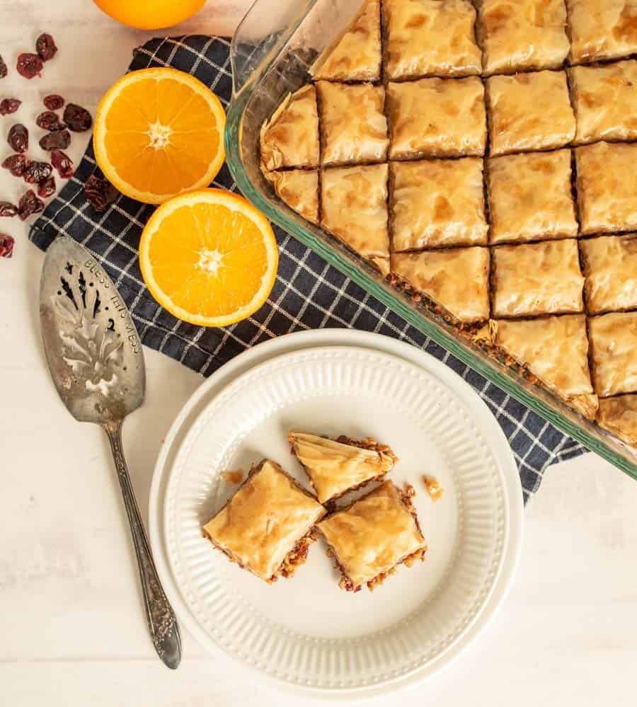 top view of a plate and pan of baklava with oranges and cranberries next to it