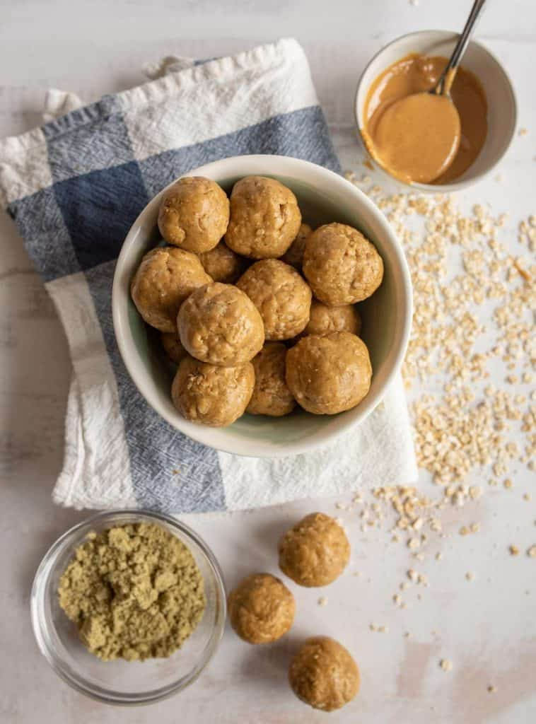 top view of peanut butter protein balls in a bowl surrounded by the ingredients for the protein balls