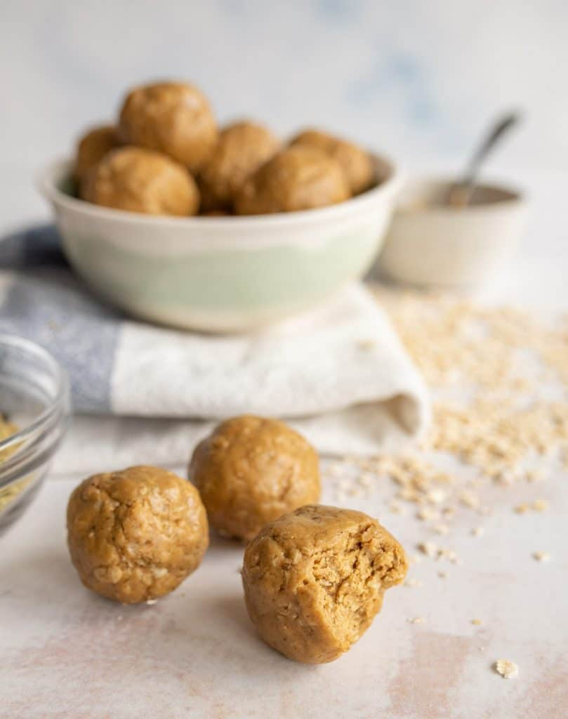 picture of peanut butter protein balls with a bowl of them in the background